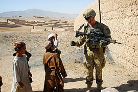 Australian Army Pvt. Levi Mooney, right, bumps fists with a child during a patrol in Tarin Kowt, Uruzgan province, Afghanistan, July 26, 2013 130726-Z-FS372-401.jpg