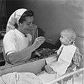 Baby wordt gevoerd door verpleegster, Bestanddeelnr 900-7985.jpg