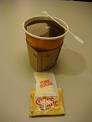 Non-dairy creamer - A cup of coffee with a sachet of sugar and a plastic sachet of Coffee-Mate non-dairy creamer
