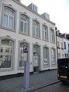 foto van Huis met brede lijstgevel, waarin een ingang en vensters met spiegelbogen in Naamse steen.