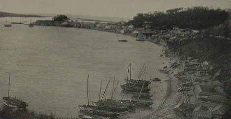 This photo shows a beach on Fusan Bay in southeast Korea. Little sail boats are anchored by the sand. No passenger or cargo ships are seen at this angle.
