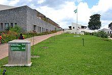 Fotografie zobrazující budovu nemocnice s rwandskou vlajkou při pohledu ze vstupní cesty