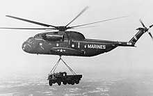 Black and white photograph of a helicopter in flight with a truck slung below it