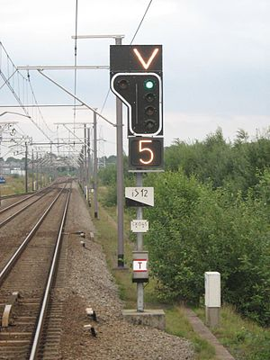 Belgian railway signalling - counter-flow track signal with a chevron and a speed restriction display (5 ⇒ 50 km/h). After this signal, the train will drive under normal track regime and cross back to the left track at 50km/h