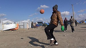 Migrants around Calais - A young migrant dribbling a ball at the camp during October 2015