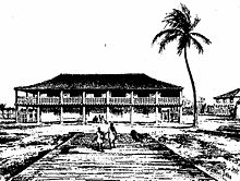 A large building in the background with the silhouette of a palm tree on the right and two people in the foreground