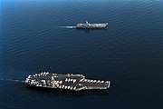 Aerial photograph of two aircraft carriers sailing in concert on calm water. The upper ship is smaller, and has a small number of aircraft on its flight deck. The larger carrier, with a flat deck crowded with planes and helicopters, is towards the bottom.