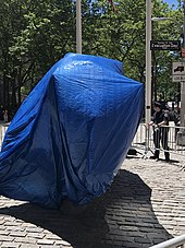 Charging Bull covered in a blue tarp and surrounded by barricades to protect it from vandalism. This photo was taken in June 2020, during the George Floyd protests in New York City.