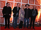 "Five people (four men, one woman in the middle) standing next to one another on a red carpet; in the background is a repeated pattern of orange blocks with the text ""meteor IRELAND MUSIC AWARDS"""