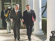Vice President Gore with President Bill Clinton walking along a colonnade at the White House.