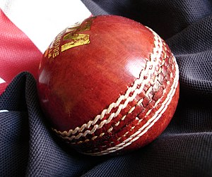 Standard cricket ball on a cricket shirt.