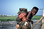 DF-ST-99-06027 - LCpl Donald Kenley carries Haitian refugee at Camp McCalla in Guantanamo Bay, Cuba.jpg