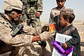 Defense.gov News Photo 110728-M-UQ450-055 - Cpl. Henry Garza a turret gunner with Company C 1st Battalion 23rd Marine Regiment helps an Afghan child learn to drink from a juice box during.jpg