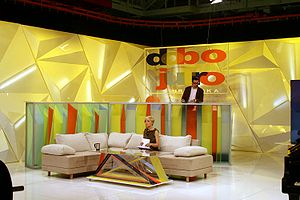 Television in Croatia - Croatian morning-show studio, with woman seated on sofa and man behind her standing at counter