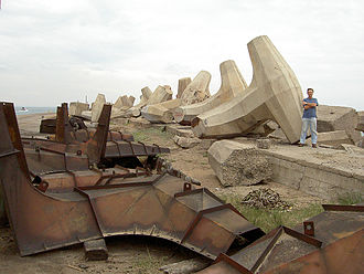 Dolos - A man stands next to a dolos, showing its relative size. Dolosse moulds are in the foreground - Durban, South Africa