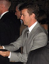 A side view of Norton in suits giving autographs