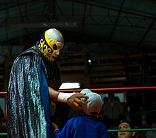 A picture of the masked wrestler El Canek giving a young fan an autograph.
