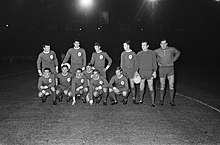 Black and white photo of a football team in kit, with a black sky in the background. Five players are crouched down, and six are standing.