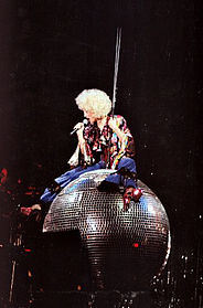 Image shows female performer sitting on a disco ball, wearing a big curly blonde wig, a maroon blouse and blue pants with red heels and is holding a microphone to her mouth.