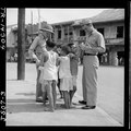 Filipino children make friends with two Naval officers in downtown Manila, hoping for a gift in return. - NARA - 520951.tif