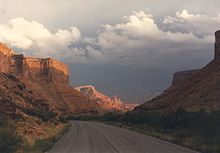 Highway through a sandstone gorge, with sunlight peering through clouds illuminating towers in the background.