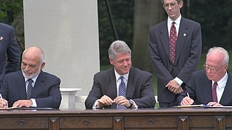 Israel–Jordan peace treaty - U.S. President Bill Clinton (center) watches Jordan's King Hussein (left) and Israeli Prime Minister Yitzhak Rabin (right) sign the Washington Declaration on the White House lawn, which ended the state of official enmity between the two countries, July 1994