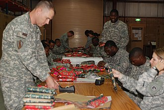 Generosity - Members of the US Army 1st Sustainment Command wrap Christmas gifts for soldiers stationed in or passing through Kuwait, 2008