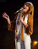 Florence Welch, in a mustard-yellow-and-white outfit, singing passionately into a microphone