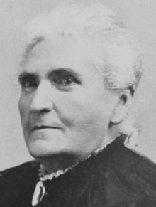 woman with white hair pulled back in black dress with white ruffles showing at collar stares sternly at camera