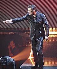 A man dressed in a black leather suit standing on a stage holding out a microphone to an audience