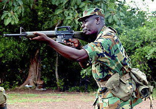A man in forest camouflage holding an assault rifle to the right side of his face and aiming it