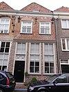 foto van Huis met schilddak en lijstgevel, met op de verdieping mozaiekversiering in baksteen, bestaande uit sterren; korfbogige ontlastingsbogen met natuursteenblokken, ankers. Winkelpui