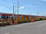 Green Line train at Airport station behind The Canyon, Aug 15.jpg