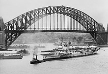 Black and white photo of a Second World War-era aircraft carrier in front of a steel through arched bridge. Several other ships are visible near the aircraft carrier