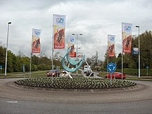 A roundabout with a sculpture in the middle of it, and banners depicting cyclists hanging around it