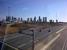 A skyline of tall buildings viewed from an overpass of a freeway