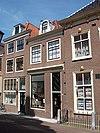 foto van Huis met eenvoudige gevel met roeden in de vensters op de enige verdieping en in bovenlicht. Pand wellicht ouder. Dakkapel