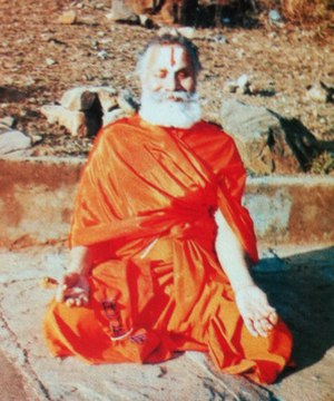 Rambhadracharya - Rambhadracharya meditating on the banks of Mandakini river during a Payovrata. He is seated in the Sukhasana pose with fingers folded in the Chin Mudra.