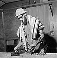 Joodse man met een hoedje op en een gebedsmantel om bezig met het aanleggen van , Bestanddeelnr 255-4704.jpg