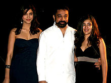 Bearded man in white, flanked by two young women in black dresses