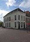 foto van Hoekpand met gepleisterde lijstgevels met smalle gevel aan de Veenestraat en zijgevel aan de Burgwal onder langgerekt schilddak