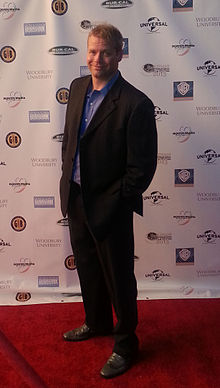 The actor Kiff VandenHeuvel is at a Redcarpet wearing a black suit and a blue shirt.