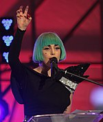A woman wearing a blue bob wig, stands talking behind a podium. She raises her right hand in a claw like shape.