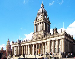 Large, rectangular, extremely ornate, marble building with many columns and other decorative details, including a columned tower on the roof.