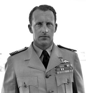 Outdoor head-and-shoulders portrait of a caucasian man in dark tie, light shirt, and light jacket with pilot's wings and medal ribbons on left-breast pocket