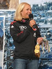 A blonde woman, wearing a predominately black jacket and blue jeans, stands in front of a large poster of a winter landscape, smiles and looks to the right. She holds a microphone in her right hand and several gold medals in her left hand.