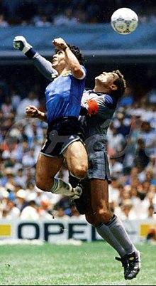 Photographie en couleurs. Deux joueurs sont en suspension pour atteindre un ballon au-dessus d'eux. Tous les deux ont un bras en l'air, tandis que Maradona a sauté plus haut que Shilton.