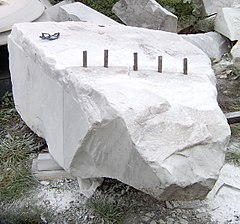 Using plug and feathers to split a block of marble from the quarry