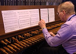 A man plays a carillon's wooden keyboard with his fists.