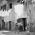 Meisje schuift wasgoed met een stok over een waslijn tussen woningen boven een s, Bestanddeelnr 254-5534.jpg